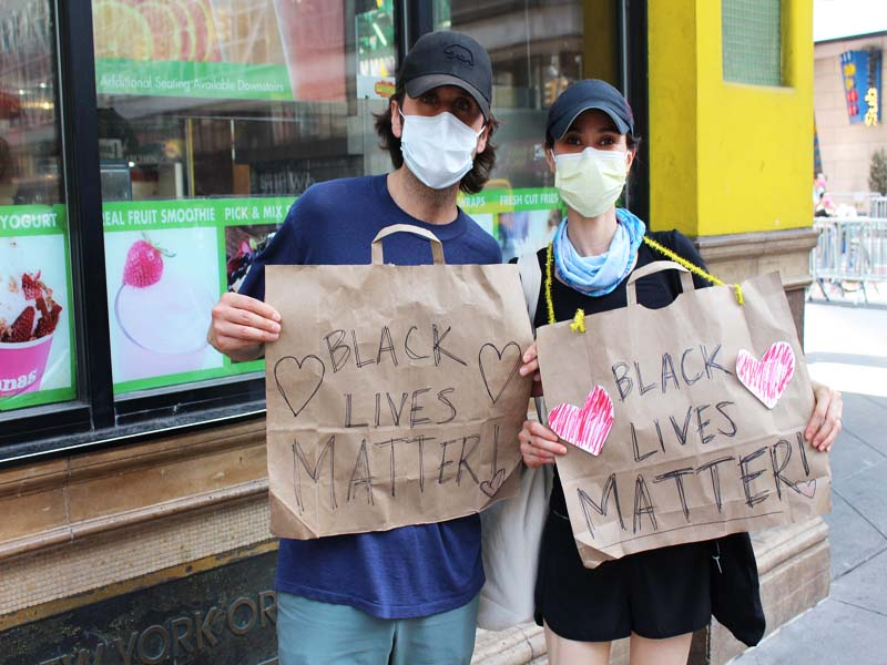 A couple holding up signs and protesting George Floyd's killing